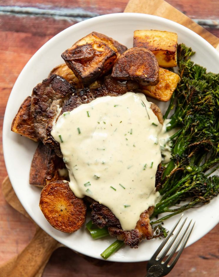 overhead shot of steak with sauce served with potatoes and broccolini on white plate
