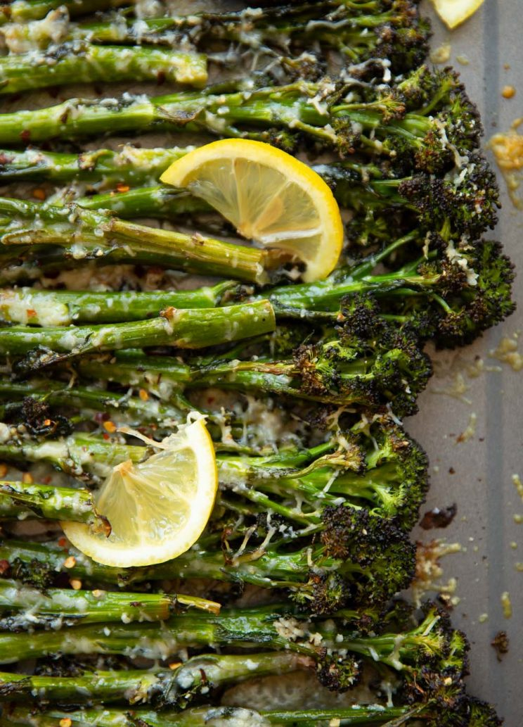 overhead shot of broccolini on grey oven tray with lemon wedges