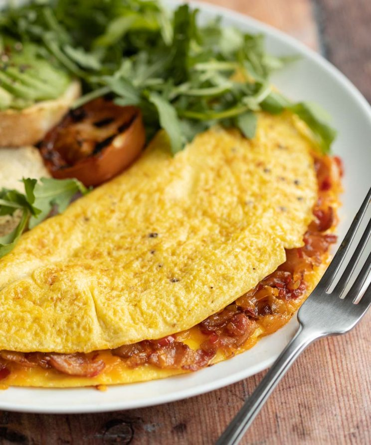 closeup shot of omelette on white plate with silver fork resting on it with salad blurred in background
