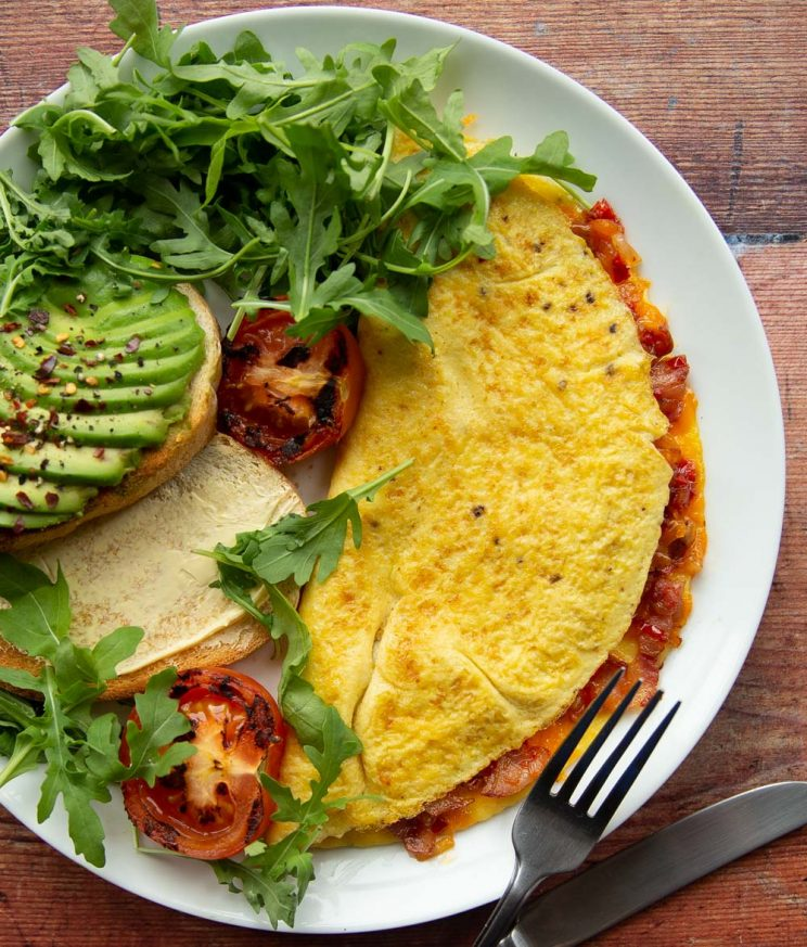 overhead shot of omelette on plate with salad, avocado and toast