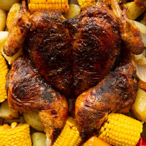 overhead shot of chicken surrounded by corn, onion and peppers on tray