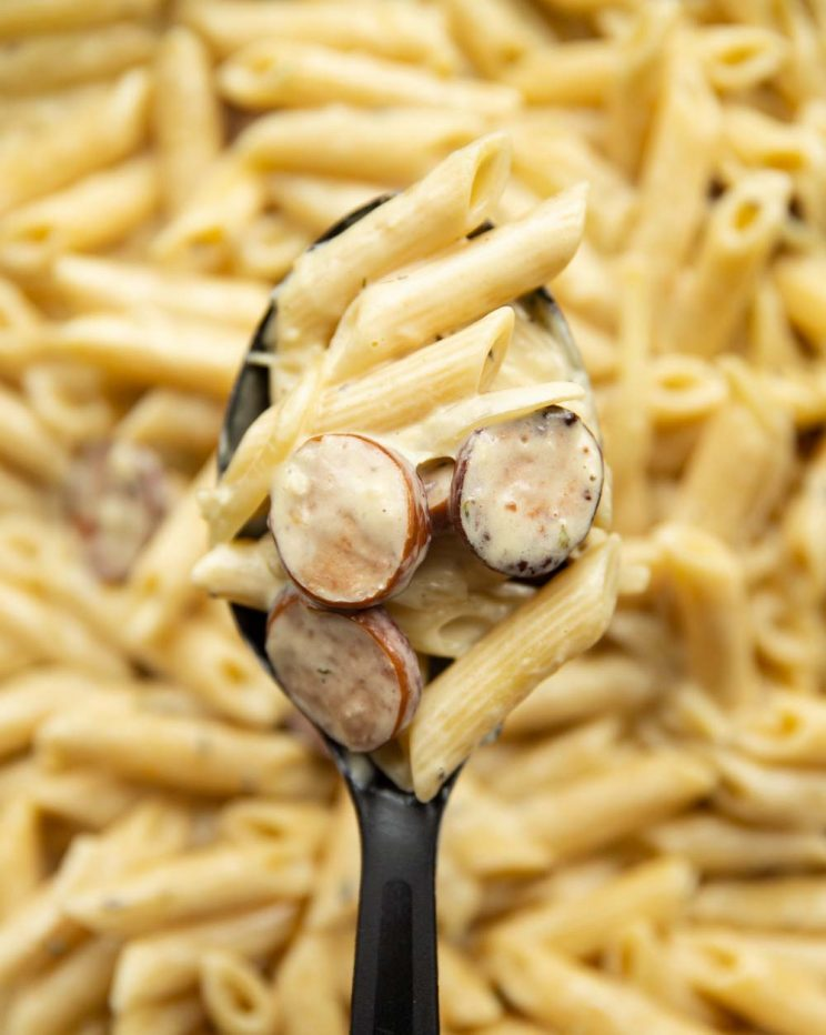 overhead shot of pasta on serving spoon with skillet of pasta blurred behind