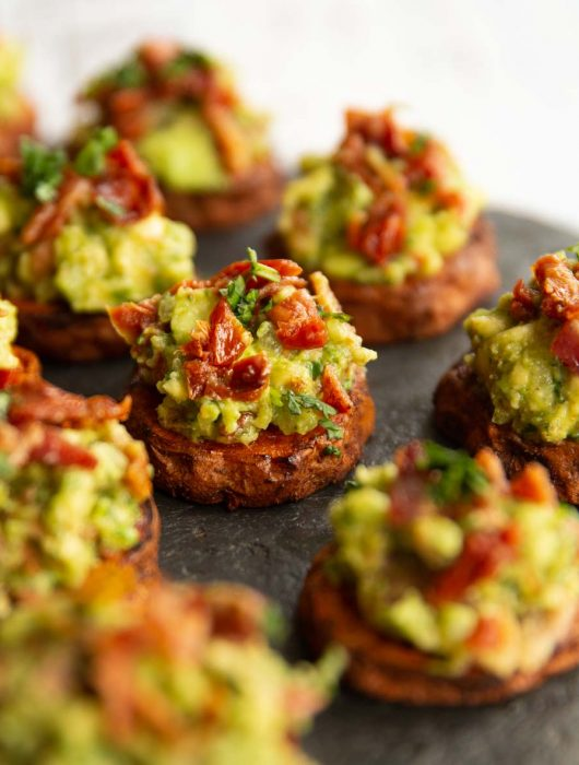 sweet potato bites on slate, focused on one in the middle garnished with coriander