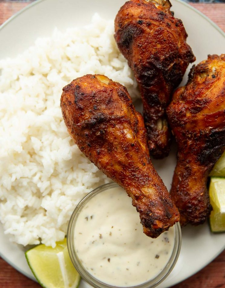 overhead shot of 3 drumsticks on white plate served with rice, ranch and lime wedges