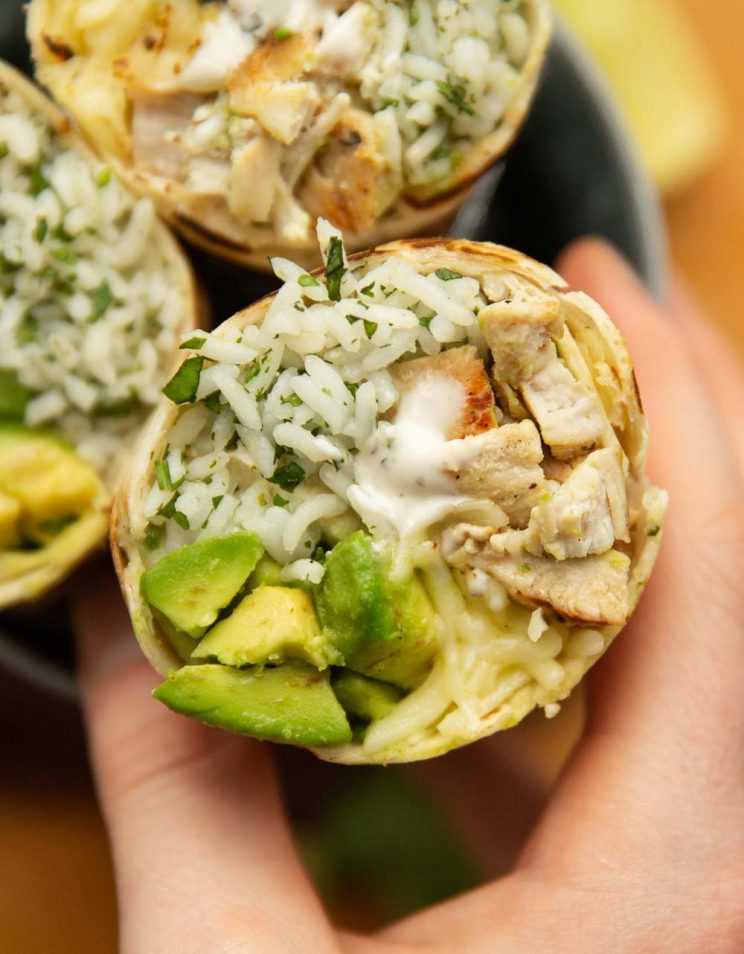 overhead shot of hand grabbing on to sliced open burrito