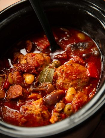 black serving spoon digging into slow cooker of chicken and chorizo