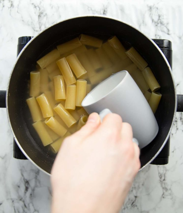 grey mug scooping into boiling pasta to collect water