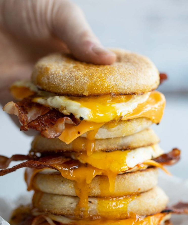 hand grabbing top sandwich of a stack with yolk dripping out