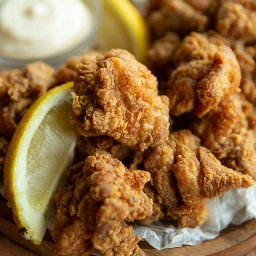 close up shot of chicken with lemon wedge on wooden board