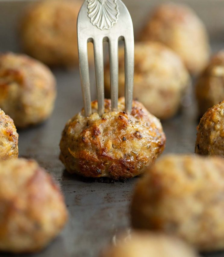 close up shot of fork digging into stuffing ball on oven tray
