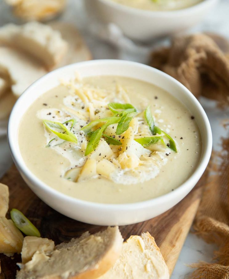 soup in a white bowl on chopping board surrounded by bread garnished with cheese, potato and spring onion