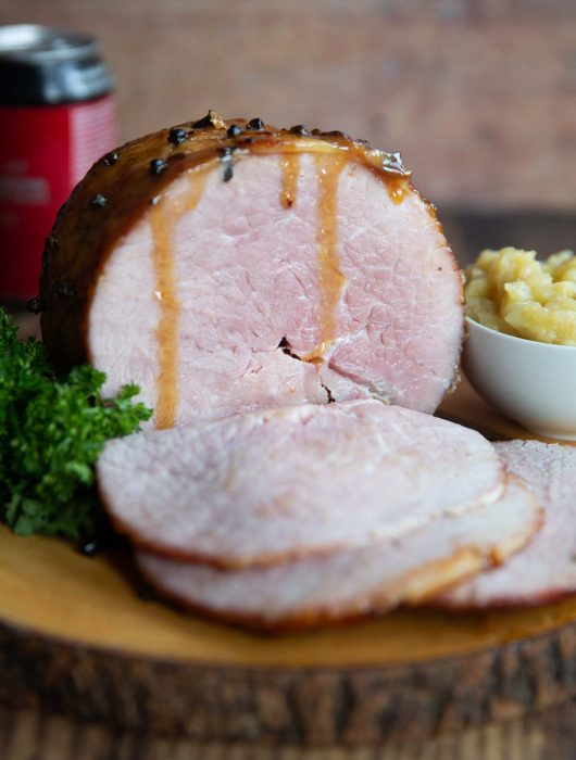 ham on wooden board next to parsley and apple sauce