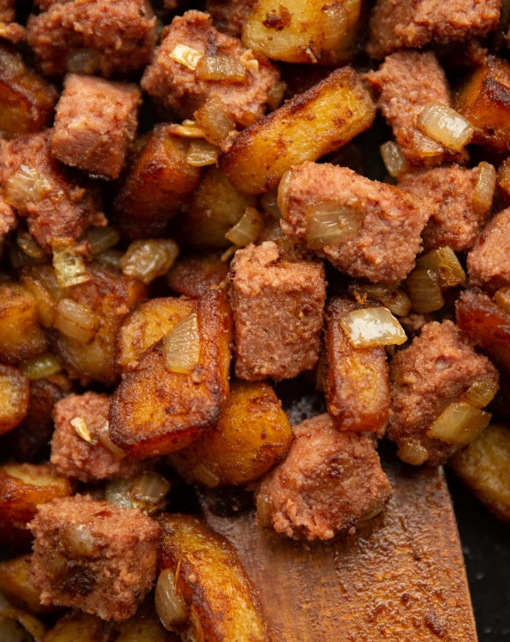 over head shot of corned beef hash in skillet with wooden spoon digging in