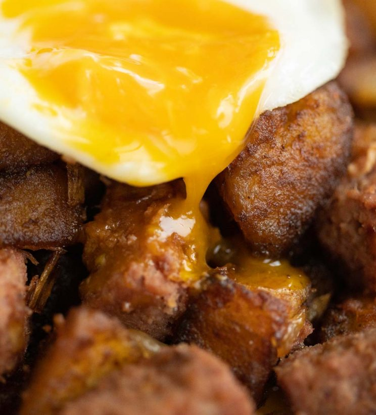 close up shot of yolk dripping down onto corned beef
