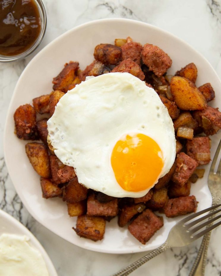 overhead shot of fried egg on corned beef hash on white plate with marble background
