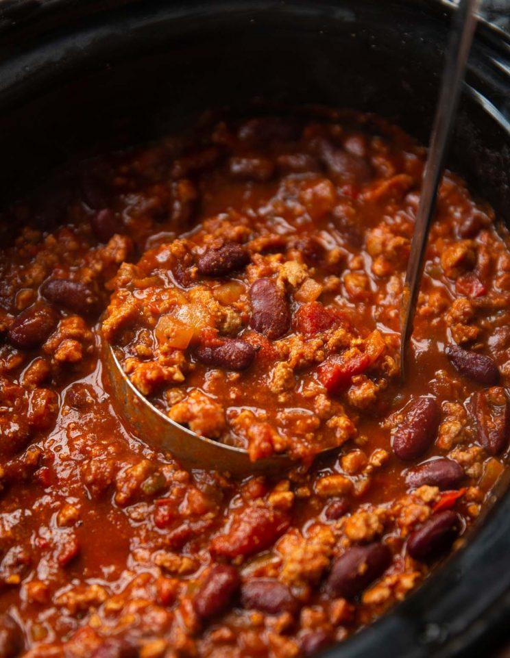close up shot of ladle in slow cooker scooping out chili