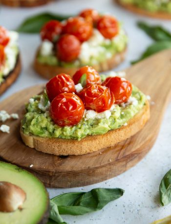 tomato avocado toast on wooden board surrounded by toast and garnish