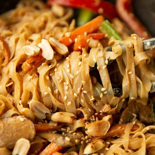 tongs twizzling noodles in wok garnished with peanuts and sesame seeds