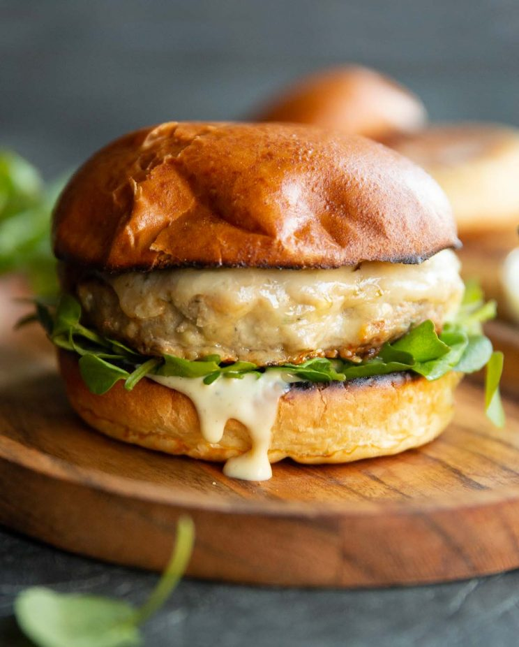 burger on small wooden board with buns and watercress blurred in background