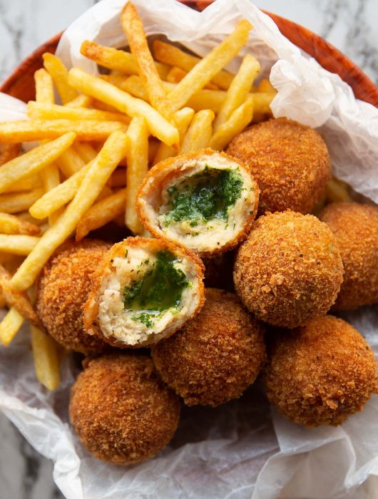 overhead shot of kievs and french fries in small bowl with a kiev split in half on top