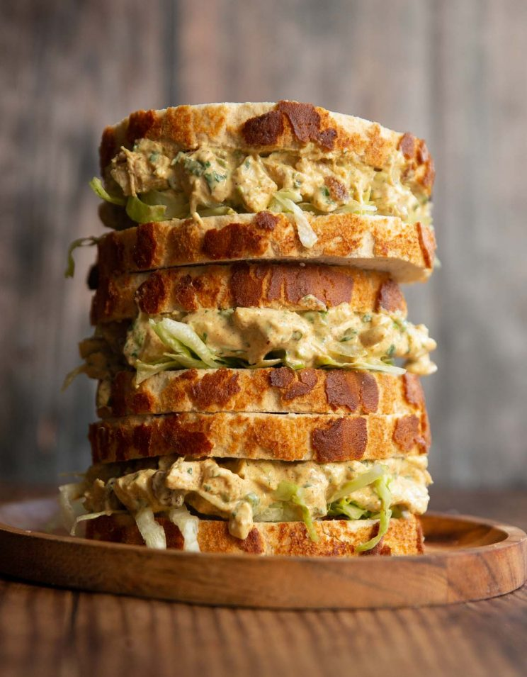 3 coronation chicken sandwiches stacked on each other on small wooden board