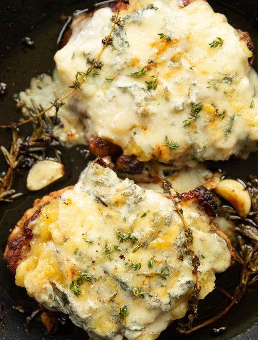 overhead shot of pork chops with applesauce and melted blue cheese in pan