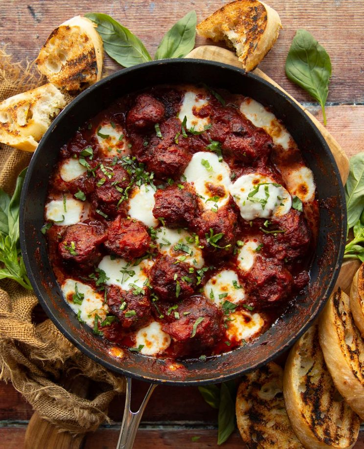 overhead shot of meatballs in skillet surrounded by fresh basil and garlic bread