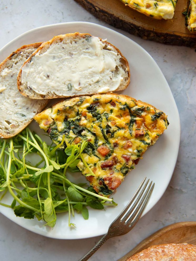 overhead shot of slice of frittata on white plate with peashoots and buttered bread