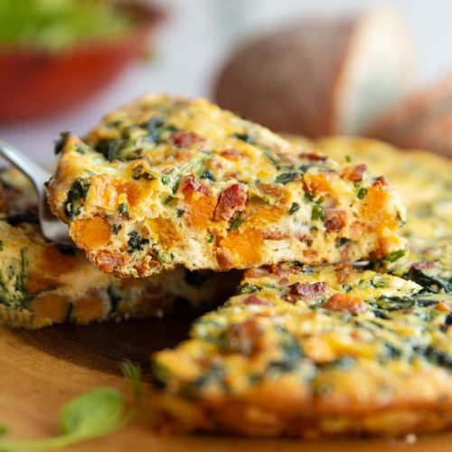 lifting slice of frittata above wooden board with salad and bread blurred in background