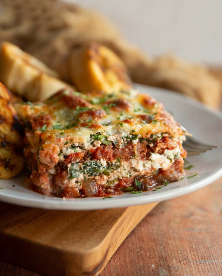 lasagne served on white plate with garlic bread blurred in background