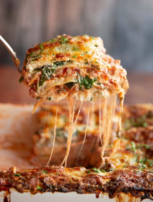 lifting lasagne from baking dish with cheese pouring down