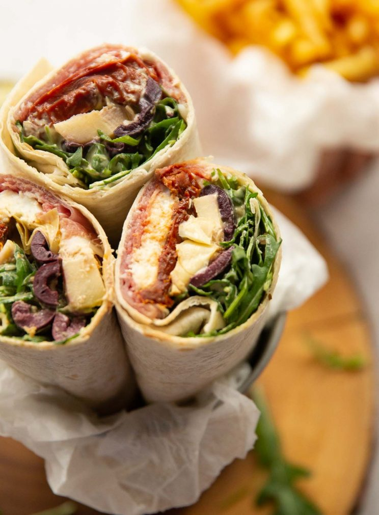 closeup shot of wrap showing filling with fries blurred in background