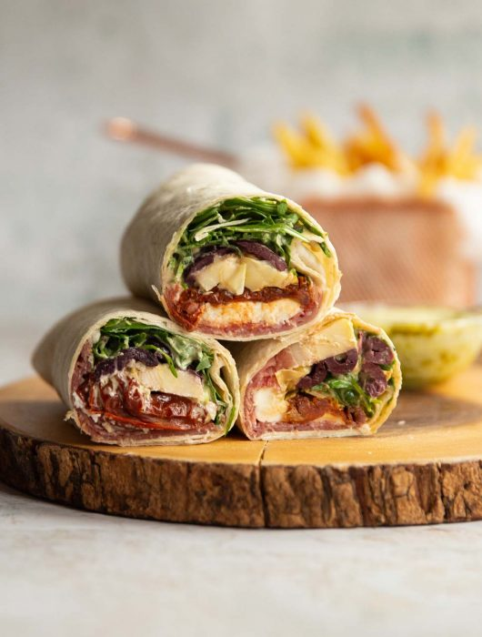 3 wraps stacked on each other on wooden board with dip and fries blurred in background