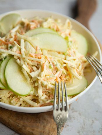 apple slaw in big white bowl with two silver forks resting on it