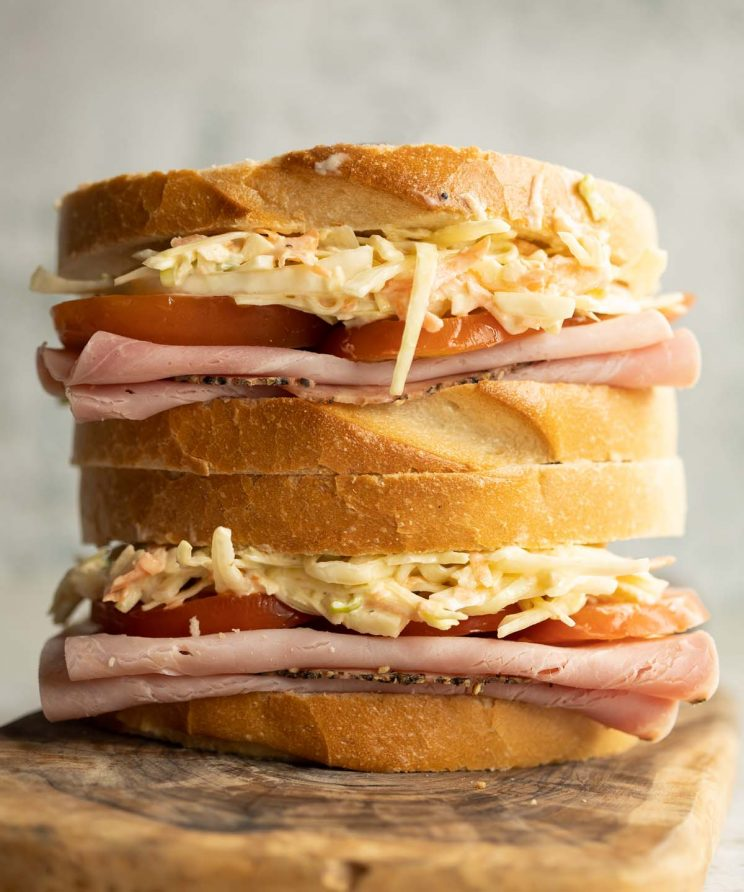 two sandwiches stacked on each other on wooden board