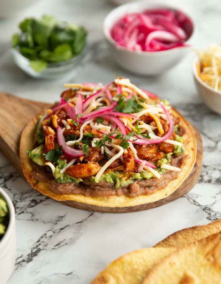 close up shot of tostada on small wooden board surrounded by toppings