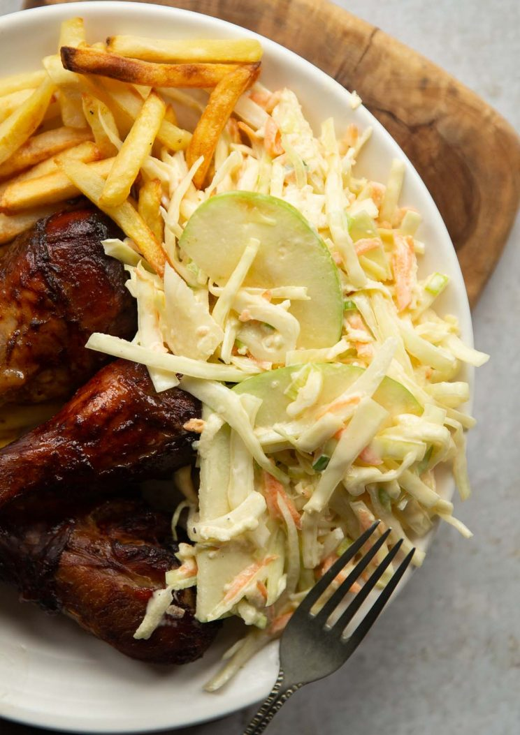 overhead shot of apple slaw, chicken drum sticks and fries on small white plate