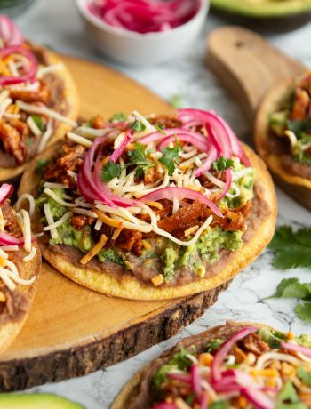 tostada on wooden board surrounded by garnish and more tostadas