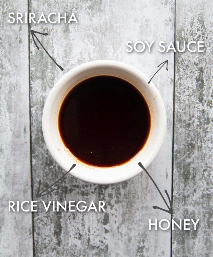 honey sriracha soy sauce in small white pot with ingredient labels