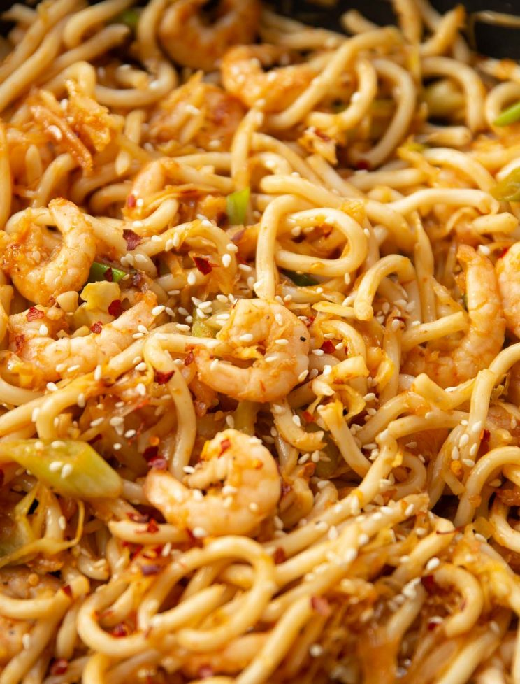 closeup shot of prawn noodles in skillet garnished with sesame seeds and chilli flakes