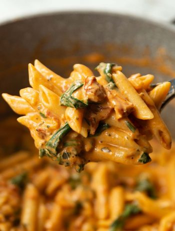 close up shot of pasta on black serving spoon above pot