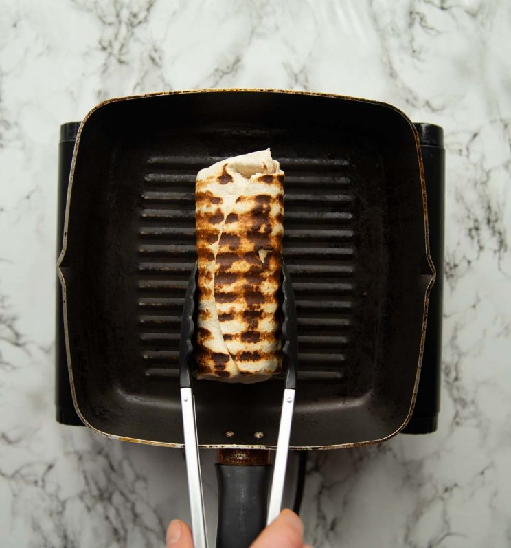 overhead shot of tongs holding toasted wrap on griddle pan