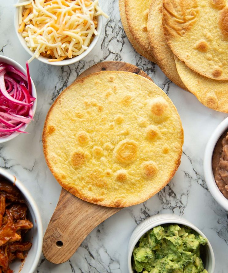 overhead shot of tostada shell surrounded by ingredients ready to make chicken tostadas
