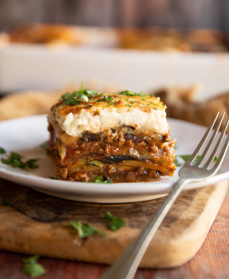 moussaka on small white plate with silver fork garnished with fresh parsley