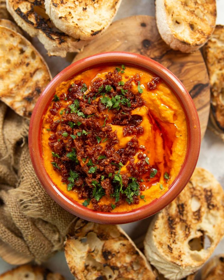 overhead shot of dip in small red bowl surrounded by toasted ciabatta