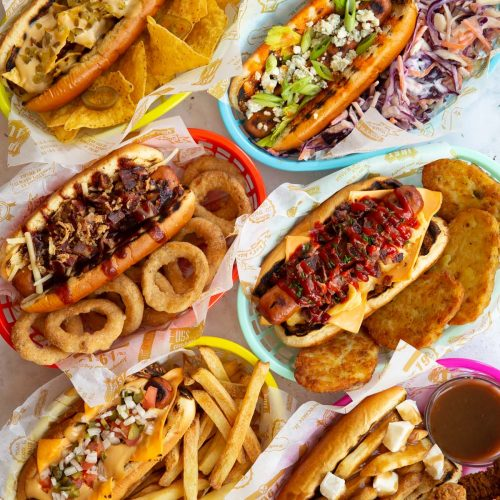 overhead shot of 6 hot dogs in coloured baskets with range of sides
