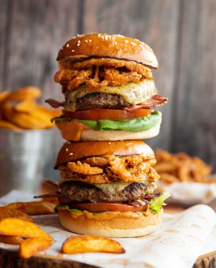 2 burgers stacked on top of each other on wooden board with fried onions and wedges blurred in background