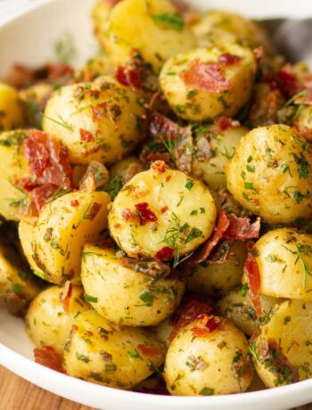 herbed potato salad served in white bowl with 2 silver spoon blurred in background