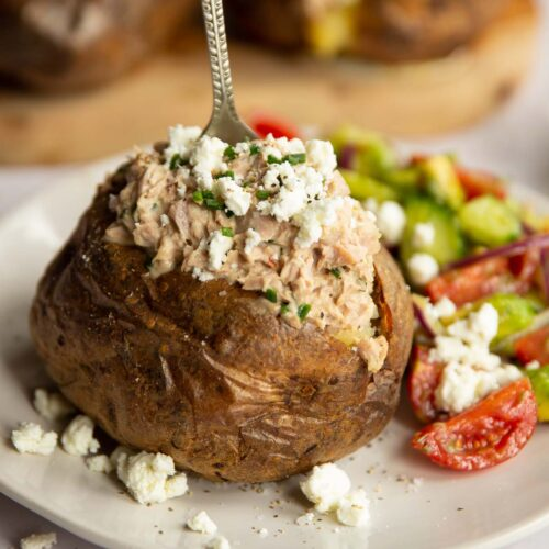 tuna baked potato on white plate with silver fork digging in next to side salad