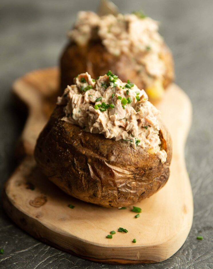 two tuna jacket potatoes on large wooden board garnished with chives